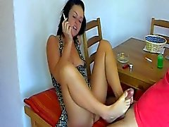 She smokes while giving a footjob