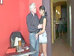 Young Barmaid Services Older Man At His Table