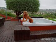 Curly hair hottie plays fucks herself with dildo in the hot tub outside