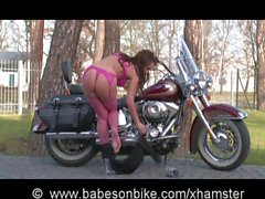 Hot Babe on Bike in latex outdoor
