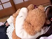 Innocent young Asian hugs her teddy bear while getting her