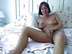 Brunette masturbates on bed