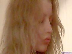 Stunning blonde teenie teasing herself on red couch