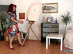 Redhead granny paints nude subjects