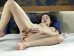 Watch brunette Xenia squeeze her upturned tits and then